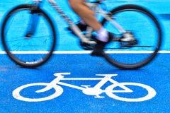 O ciclista masculino monta uma bicicleta na pista do sinal da bicicleta fotos de stock