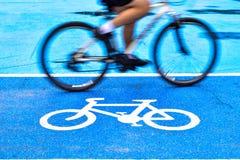 O ciclista masculino monta uma bicicleta na pista do sinal da bicicleta fotos de stock royalty free