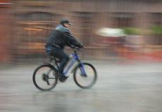 O ciclista monta através das ruas em um dia chuvoso fotos de stock