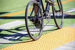 O ciclista monta a bicicleta ao longo de trajeto de ciclagem especialmente marcado na estrada fotos de stock