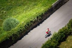 O ciclista monta um Mountain bike com suspensão completa ao longo de uma estrada asfaltada ao longo das plantações verdes acima V foto de stock