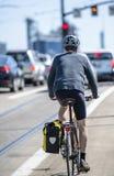 O ciclista no capacete aumenta na maneira acima para trajeto dedicado da bicicleta e cercada pelo outro tráfego imagens de stock