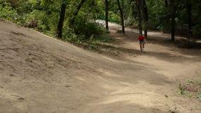 O ciclista no uniforme azul vermelho na bicicleta amarela aumenta acima monte vídeos de arquivo