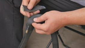 O ciclista ou o mecânico limpam uma bicicleta puncionada do pneu Feche acima das m?os e bicycle o pneum?tico do pneu liso Um home video estoque