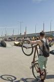 O ciclista que abraça a bicicleta está de espera o começo do compet Fotos de Stock Royalty Free