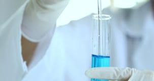 O cientista agita o líquido azul no tubo de ensaio filme