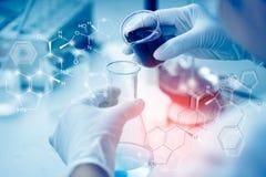 O cientista asiático novo é determinadas atividades na ciência experimental como produtos químicos ou os dados de mistura da entr foto de stock