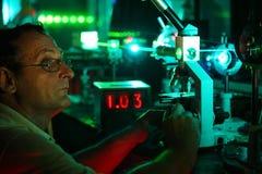 O cientista com vidro demonstra o laser fotos de stock royalty free