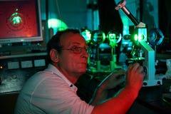 O cientista com vidro demonstra o laser Imagens de Stock Royalty Free