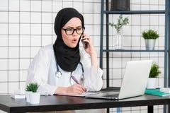 O cientista encoberto fêmea que senta-se em sua mesa que olha o portátil abre sua boca com emoção chocada da cara ao falar sobre fotos de stock royalty free