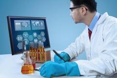 O cientista escreve o relatório da pesquisa imagem de stock
