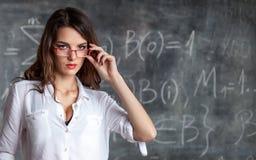 O cientista fêmea atrativo esperto nos vidros aproxima o quadro-negro Fotografia de Stock Royalty Free