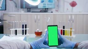 O cientista guarda um smarphone com o modelo verde isolado da tela filme