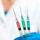 O cientista mantem a injeção três enchida com o verde, o vermelho, e o azul Foto de Stock