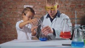 O cientista masculino com estudante pequena conduz uma experiência química junto filme