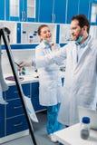 o cientista no branco reveste perto da placa para as notas que têm a discussão durante o trabalho foto de stock royalty free