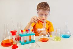 O cientista novo em óculos de proteção de segurança estuda a prática química no laboratório Imagens de Stock