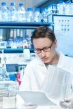 O cientista novo ou a tecnologia trabalham no laboratório moderno Imagens de Stock