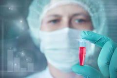 O cientista ou a tecnologia guardam a amostra biológica líquida Fotografia de Stock