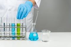 O cientista que põe o tubo de ensaio na cremalheira fotografia de stock