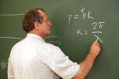 O cientista resolve a equação no quadro-negro imagem de stock