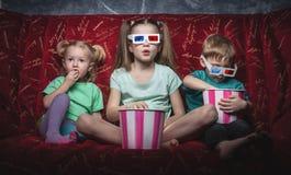 O cinema das crianças: As crianças sentam-se em um sofá vermelho e olham-se um filme 3D fotografia de stock royalty free