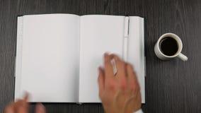 O cinza cobriu o bloco de notas e o copo do cofee no fundo de madeira escuro Abrindo um bloco de notas para escrever video estoque