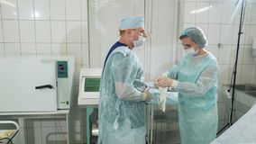 O cirurgião calça luvas limpas antes da operação, as ajudas que da enfermeira o doutor as pôs sobre Os doutores estão preparando- video estoque