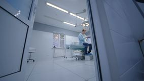 O cirurgião examina o paciente em uma sala de operações moderna video estoque