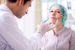 O cirurgião plástico que prepara-se para a operação na cara da mulher imagens de stock royalty free
