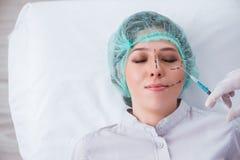 O cirurgião plástico que prepara-se para a operação na cara da mulher fotos de stock