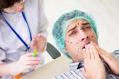 O cirurgião plástico que prepara-se para a operação na cara do homem imagem de stock royalty free