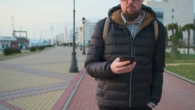 O citadino está andando na área pedestre da cidade no dia do outono, guardando o smartphone video estoque