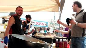 O cliente dá o dinheiro ao vendedor do alimento, alimento oriental, rolo com carne na grade, shawarma, um homem com uma barba filme