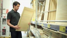 O cliente do homem na loja do hardware escolhe obturadores de madeira para sua casa video estoque