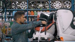 O cliente escolhe o assento da criança no supermercado Homem na loja do carro que escolhe o babyseat da segurança das crianças video estoque