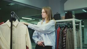 O cliente fêmea atrativo está escolhendo a blusa e a saia na sala de encaixe filme