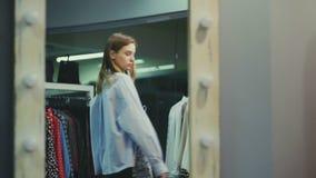 O cliente fêmea atrativo está escolhendo a saia na sala de encaixe filme