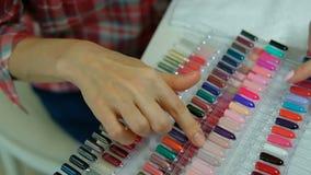 O cliente fêmea escolhe uma cor de uma grande paleta para o tratamento de mãos vídeos de arquivo