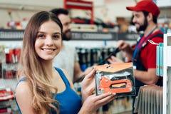 O cliente fêmea está levantando com o grampeador novo na loja das ferramentas elétricas imagens de stock