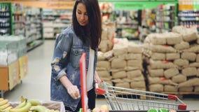 O cliente feliz da mulher bonita está comprando o fruto no supermercado que escolhe bananas e maçãs e que põe os no carrinho de c video estoque