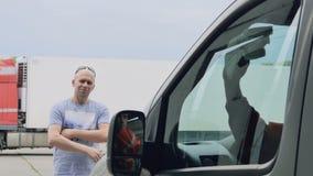 O cliente feliz ocupa da cabine do carro dos polimentos do trabalhador e do polegar da mostra acima vídeos de arquivo