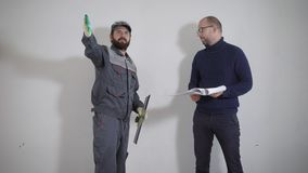 O cliente funde com o construtor sobre o reparo de seu apartamento, os homens está falando no local vídeos de arquivo