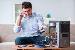 O cliente irritado que tenta reparar o computador com apoio do telefone imagens de stock