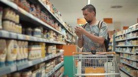 O cliente masculino está lendo etiquetas em frascos e em garrafas em um supermercado filme
