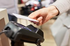 O cliente paga com o cartão de crédito de NFC foto de stock