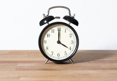 It is 4:00 o`clock. The time is four o`clock. A retro clock isolated on a wooden table and white background Royalty Free Stock Image