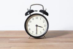 It is 3:30 o`clock. The time is half past four. A retro clock isolated on a wooden table and white background Royalty Free Stock Images