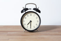 It is 07:30 o`clock. The time is half past seven o`clock. A retro clock isolated on a wooden table and white background Stock Photo