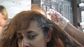 O close-up, o cabeleireiro aplica a pintura ao cabelo de uma menina da nacionalidade oriental durante o procedimento da coloração video estoque